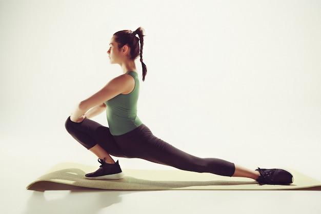 Piękna szczupła brunetka robi niektóre ćwiczenia rozciągające w siłowni