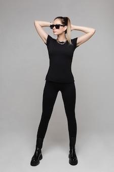 Piękna szczupła dama w totalnie czarnych ubraniach, w ciemnych okularach przeciwsłonecznych i patrząca w dal. koncepcja mody