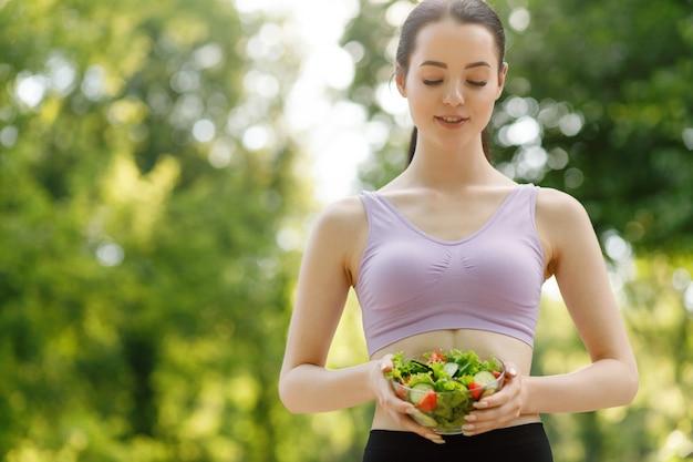 Piękna szczupła dziewczyna jedzenie sałatki na zielonym tle naturalnych.