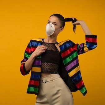 Piękna szczupła dziewczyna modelka pozowanie w respiratorze na żółtym tle. kurtka w tęczowym kolorze społeczności lgbt