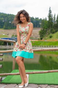 Piękna szczupła dziewczyna pozuje w zielonym letnim parku obok stawu.