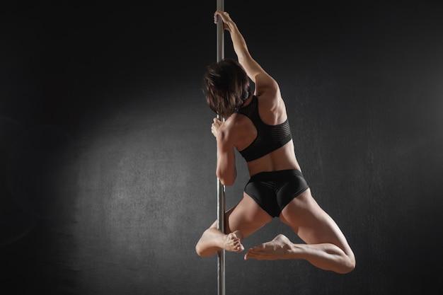 Piękna szczupła dziewczyna z pylon taniec na rurze żeński tancerz