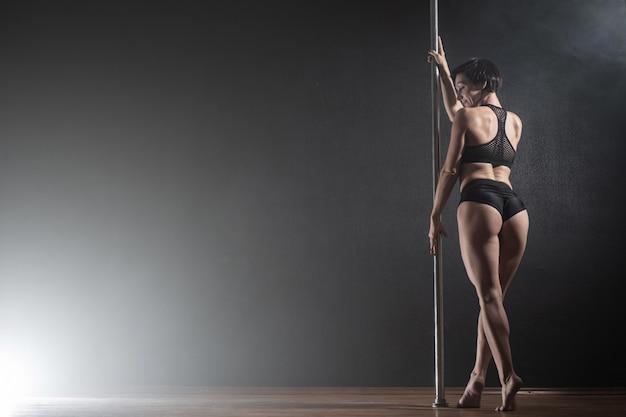 Piękna szczupła dziewczyna z pylonem. żeński tancerza słupa taniec na czarnym tle