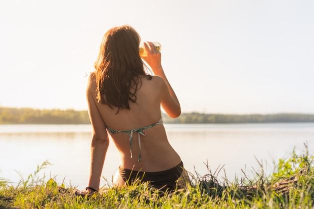 Piękna szczupła kobieta cieszy się napój blisko jeziora przy zmierzchem ciepłe słoneczne popołudnie. potomstwa dostosowywali kobiety pije lemoniadę przy brzeg rzeki