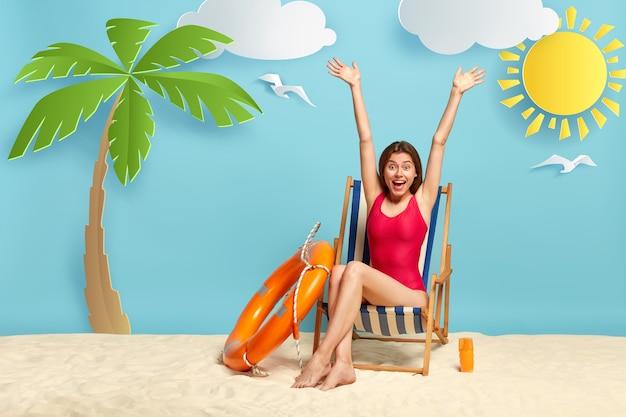 Piękna szczupła kobieta podnosi ręce, siedzi na leżaku na plaży, nosi czerwone stroje kąpielowe, cieszy się wakacjami, używa balsamu do opalania skóry