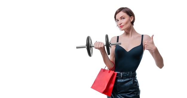 Piękna szczupła kobieta pozuje w studio z hantle i torby na prezenty
