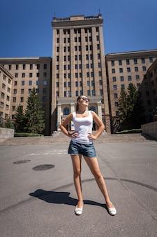 Piękna szczupła kobieta stojąca na ulicy przed wysokim budynkiem