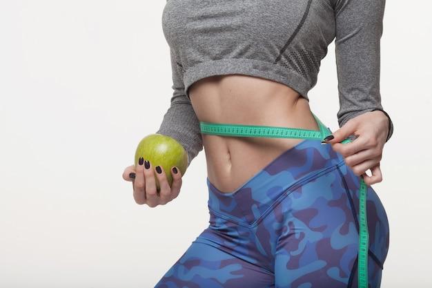 Piękna szczupła kobieta trzyma zielone jabłko i ma kilka kolorowych taśm mierniczych w talii