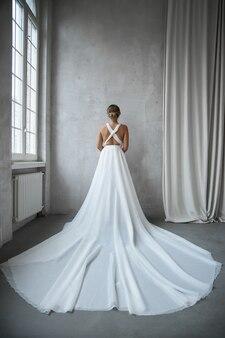 Piękna szczupła kobieta w białej sukni ślubnej, nowa kolekcja sukienek dla panny młodej. hałas, nieostry
