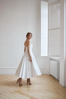 Piękna szczupła kobieta w białej sukni ślubnej, nowa kolekcja sukienek dla panny młodej
