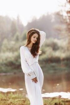 Piękna szczupła kobieta w długiej białej sukni spaceruje rano nad jeziorem