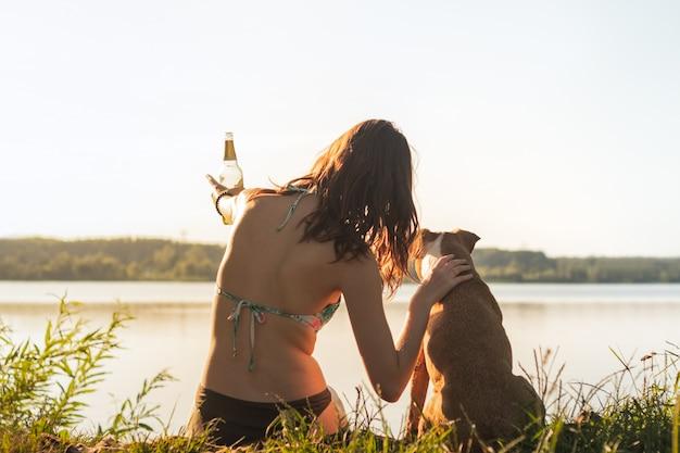 Piękna szczupła kobieta z psem, ciesząc się piękny widok w pobliżu jeziora o zachodzie słońca ciepłe słoneczne popołudnie. potomstwa dostosowywali kobiety ma napoju bezalkoholowego przy brzeg rzeki i ściska jej staffordshire teriera psa