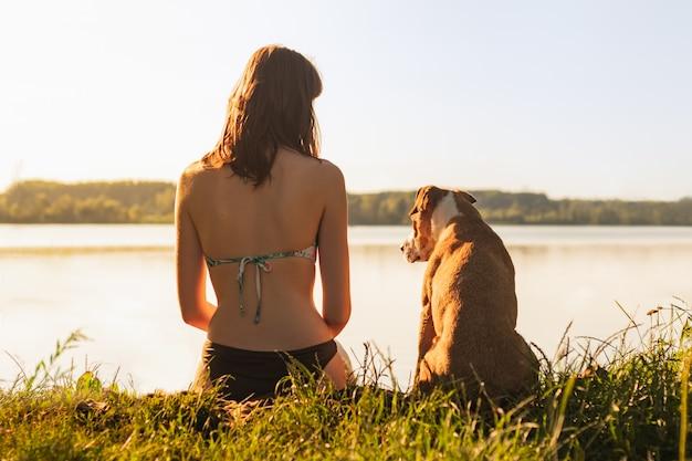 Piękna szczupła kobieta z psem, ciesząc się piękny widok w pobliżu jeziora o zachodzie słońca ciepłe słoneczne popołudnie. potomstwa dostosowywali żeńskiego obsiadanie z staffordshire teriera psem przy brzeg rzeki