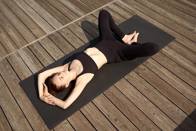 Piękna szczupła młoda kobieta medytacji, relaksu i praktyki jogi na drewnianym molo w pobliżu jeziora.