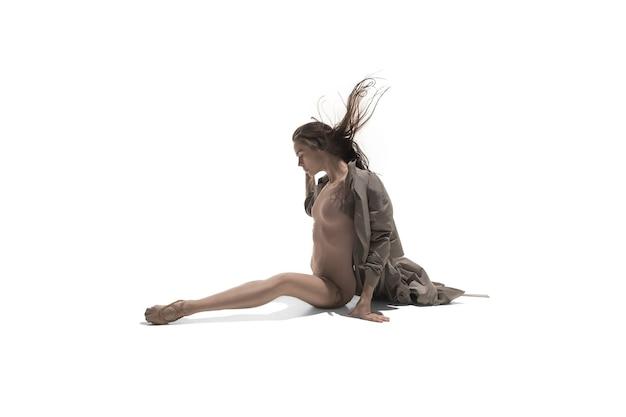 Piękna szczupła młoda kobieta nowoczesny jazz w stylu współczesnym tancerz baletowy w sylwetce na sobie beżowy długi płaszcz na białym tle na białym tle studyjny