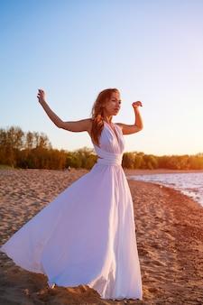 Piękna szczupła młoda kobieta pochodzenia kaukaskiego z długimi włosami stoi w białej sukience w...