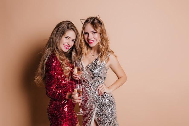 Piękna szczupła młoda kobieta z radosną miną, ciesząc się wspólną sesją zdjęciową z przyjacielem w nowym roku