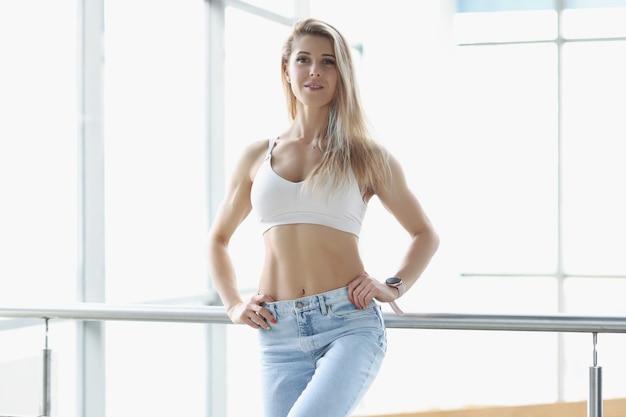 Piękna szczupła sportowa blondynka w niebieskich dżinsach i górze. koncepcja sportowego stylu życia