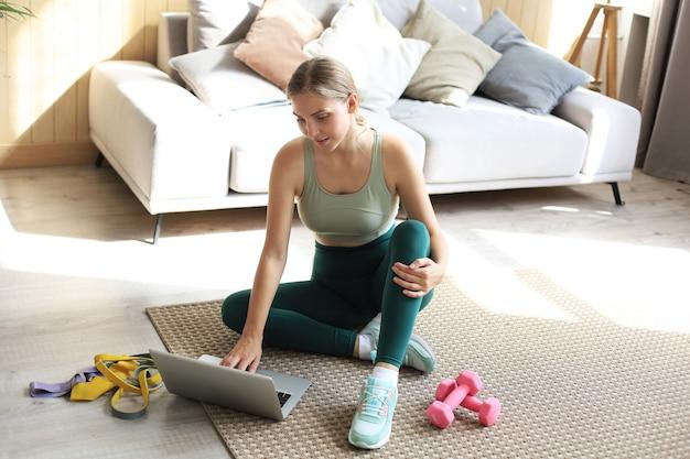 Piękna szczupła sportowa kobieta w stroju sportowym siedzi na podłodze z hantlami i używa laptopa w domu w salonie. zdrowy tryb życia. pozostań w domu.