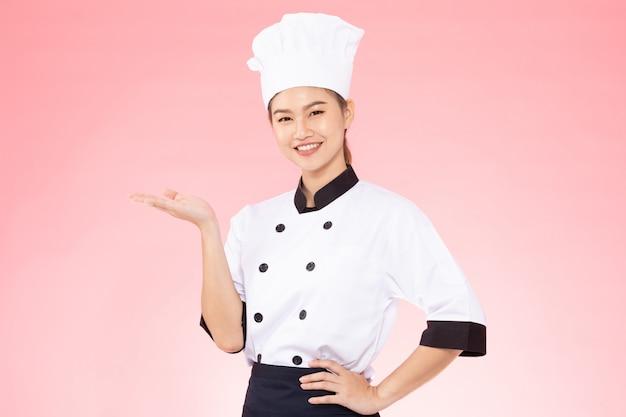 Piękna szef kuchni kobieta ono uśmiecha się na różowym tle