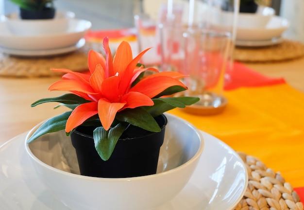 Piękna sztuczna roślina z pomarańczowymi kwiatami na stole
