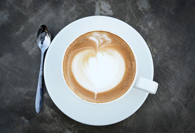 Piękna sztuka gorąca latte kawa w białej filiżance na cemencie zgłasza tło, odgórny widok