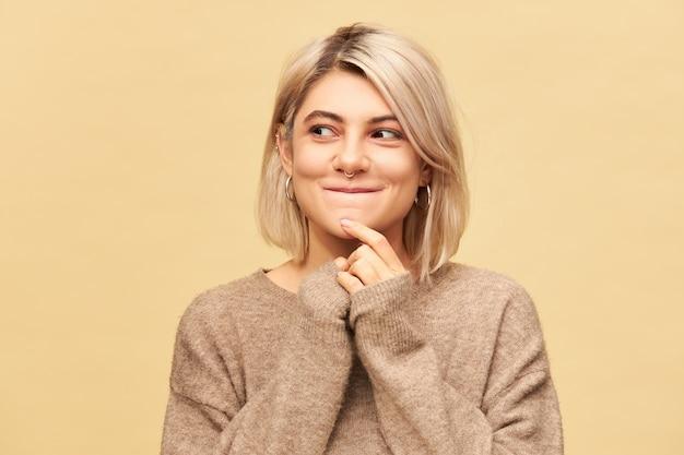 Piękna tajemnicza europejska dziewczyna w stylowym, przytulnym swetrze, zdumiona tajemniczym wyrazem twarzy, odwracająca wzrok i uśmiechnięta, wpadająca na pomysł, myśląca o planie izolowanym przy pustej ścianie