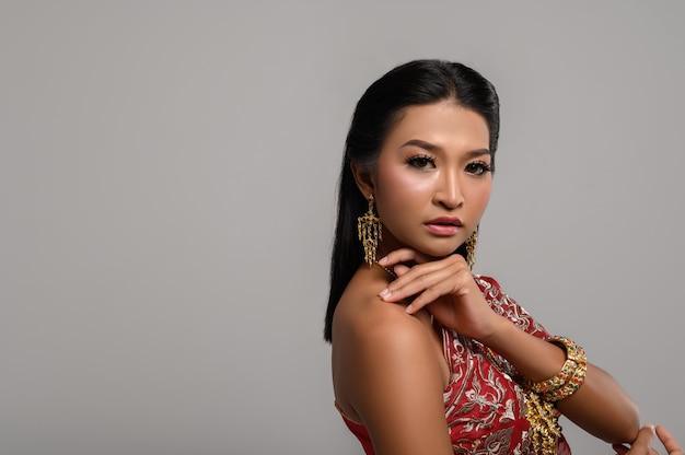 Piękna tajlandzka kobieta jest ubranym tajlandzką suknię i patrzeje strona