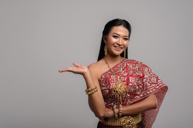 Piękna tajlandzka kobieta jest ubranym tajlandzką suknię i szczęśliwego uśmiech.