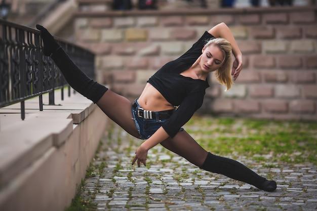 Piękna tancerka baletowa lub taniec akrobatyczny na świeżym powietrzu na ulicy