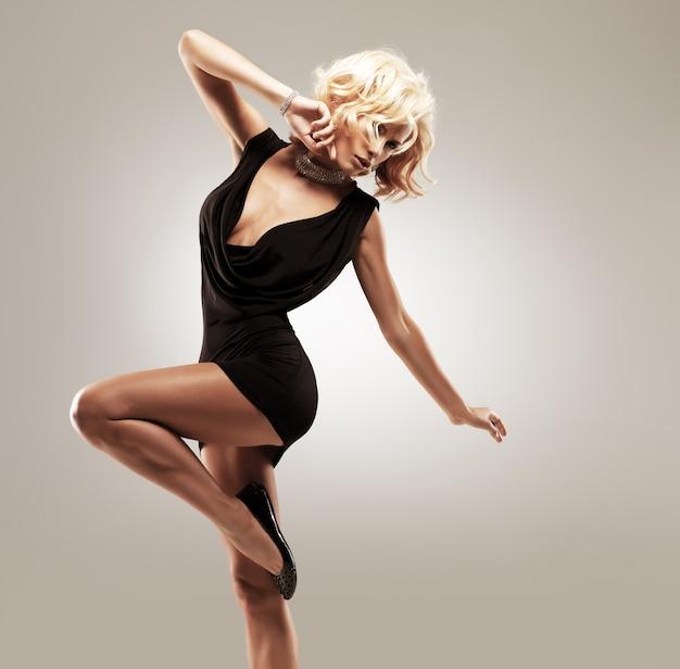 Piękna tancerka w czarnej sukni, pozowanie w studio