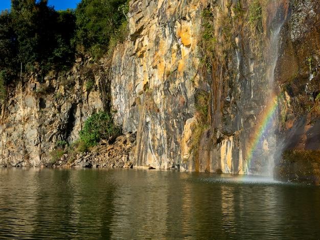 Piękna tęcza nad wodą obok skał