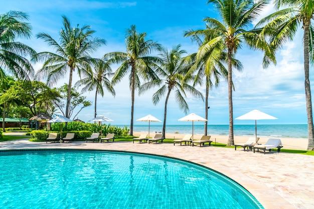 Piękna tropikalna plaża i morze z parasolem i krzesłem wokół basenu w hotelowym kurorcie na letnie wakacje
