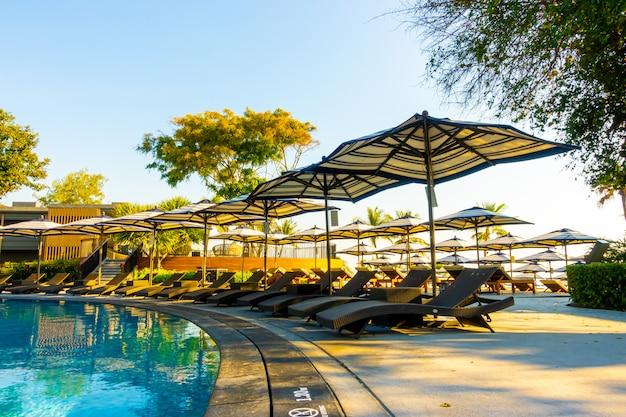 Piękna tropikalna plaża i morze z parasolem i krzesłem wokół basenu w hotelowym kurorcie na podróże i wakacje