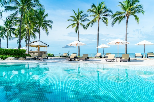 Piękna tropikalna plaża i morze z parasolem i krzesłem wokół basenu w hotelowym kurorcie