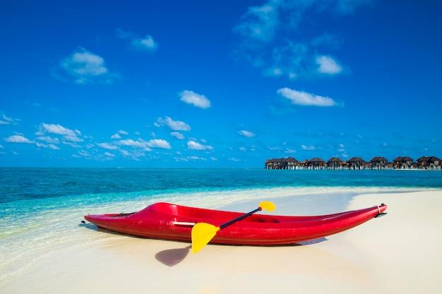 Piękna tropikalna plaża z białym piaskiem, turkusową oceaniczną wodą i niebieskim niebem na egzotycznej wyspie. kajaki na tropikalnym niebie beachue na egzotycznej wyspie. kajak plażowy