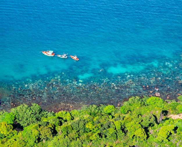 Piękna tropikalna wyspa z błękitną czystą wodą i granitowymi kamieniami. wybrzeże oceanu i łodzie. widok z góry.