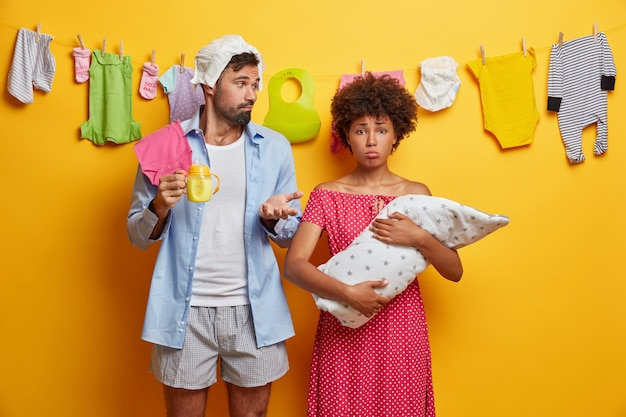 Piękna trzyosobowa rodzina pozuje w domu. smutna mama nosi córeczkę, zaintrygowany ojciec trzyma butelkę do karmienia i ubranka dla noworodka. nowożeńcy zajęci karmieniem noworodkiem.