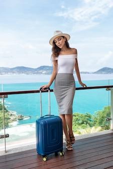 Piękna turystka z luksusową postacią w kapeluszu pozuje z balkonem na bagaż, z którego roztacza się piękny widok na morze i góry. podróże i wakacje.
