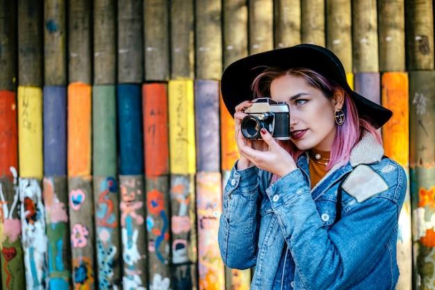 Piękna turystyczna dziewczyna jest ubranym kapelusz i drelichową kurtkę bierze fotografię.