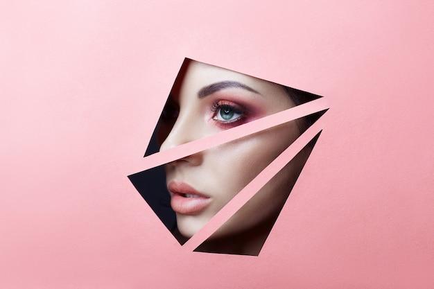 Piękna twarz czerwony makijaż oczy młoda dziewczyna w szczelinie otwór różowy czerwony papier.