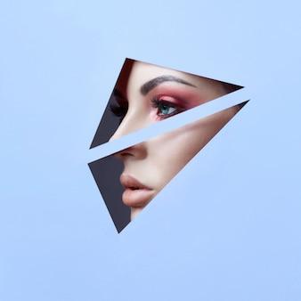 Piękna twarz czerwony makijaż oczy młodej dziewczyny w szczelinie niebieskiego papieru. kobieta z pięknym makijażem czerwony świecący cień, duże niebieskie oczy w otworze szczeliny. reklama
