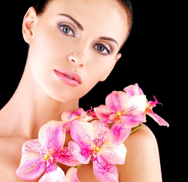 Piękna twarz dorosłej kobiety ze zdrową skórą i różowymi kwiatami na ciele - studio