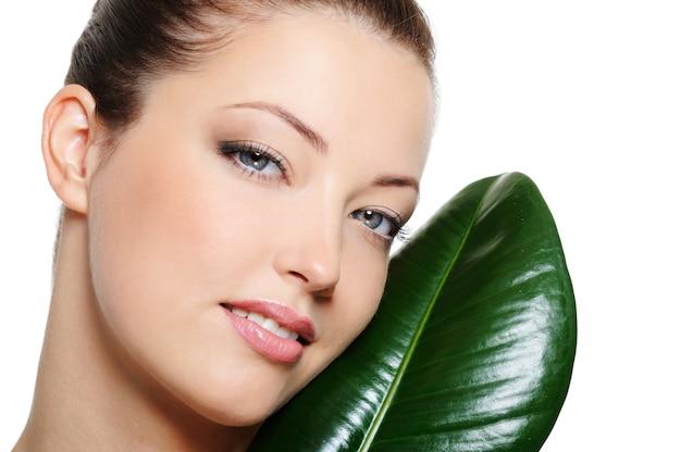 Piękna twarz jasnej kobiety w pobliżu zielonych liści na białym tle