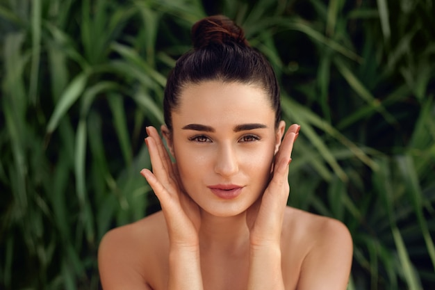 Piękna twarz. kobieta dotyka portret zdrowej skóry. piękny szczęśliwy model dziewczyny z świeżą skórą twarzy. koncepcja pielęgnacji skóry