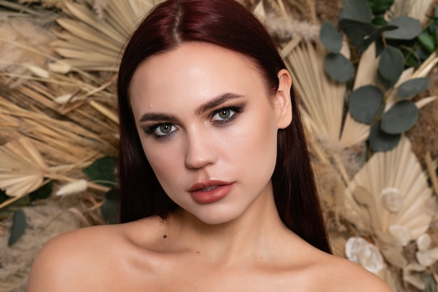Piękna twarz kobiety czysta skóra piękne kobiece oczy oczy usta doskonały zdrowy odcień skóry. kosmetologia brunetka dziewczyna z bordowymi ustami na tle wiosennych kwiatów polnych suchych. otwarte ramiona