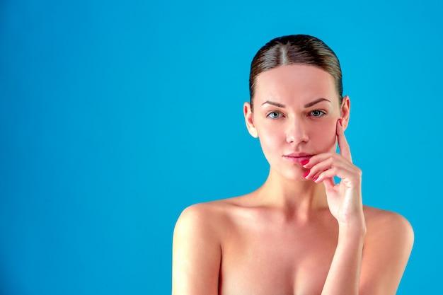 Piękna twarz kobiety portret. beautiful spa model girl with perfect fresh clean skin. brunetki żeńska patrzeje kamera i ono uśmiecha się. koncepcja pielęgnacji młodzieży i skóry. niebieskie tło szare.