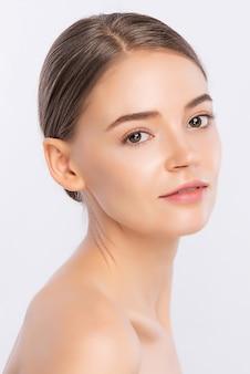 Piękna twarz kobiety portret, piękna młoda kobieta z czystą świeżą zdrową skórą, zabieg na twarz. kosmetologia, uroda i spa, na białym tle na białej ścianie