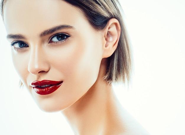 Piękna twarz kobiety portret. piękny model dziewczyna z idealną świeżą czystą skórą kolor usta fioletowy czerwony. blond brunetka krótkie włosy młodzieży i koncepcja pielęgnacji skóry. pojedynczo na białym tle