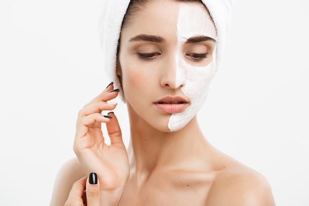 Piękna twarz kobiety rasy kaukaskiej stosowania kremu maska na jej twarzy skóry białe tło.